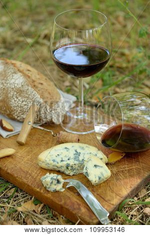 Picnic composition of red wine, delicious cheese, nuts and bread on wooden board, outdoors