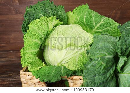 Savoy cabbage in wicker basket on wooden background, close up