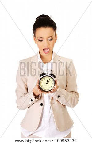 Shocked african businesswoman with alarm clock.