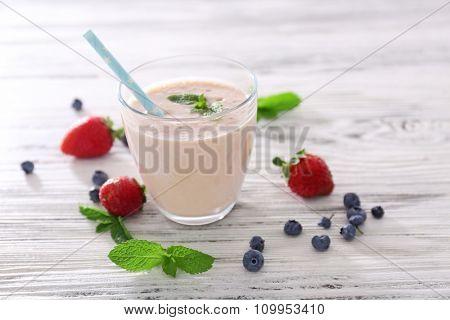 Fresh strawberry yogurt with berries around on light wooden background