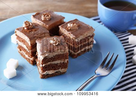 Sweet chocolate cake on blue plate on wooden table
