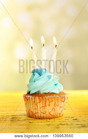 Sweet cupcake with candles on yellow wooden table against blurred background
