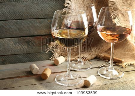 Composition of wine glasses and corks on wooden background