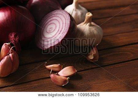 Fresh red onions with garlic on wooden background
