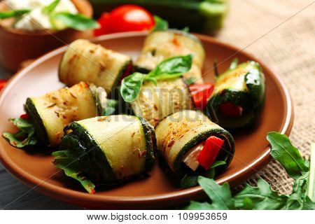 Salad with arugula and zucchini rolls on plate, on table background