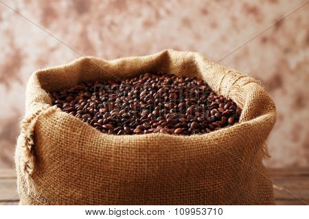Sac with roasted coffee beans on light-brown background