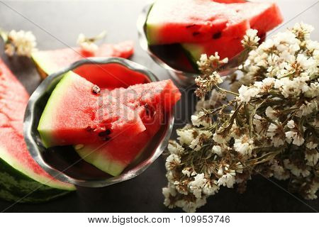 Sliced watermelon in metal bowl with flowers on grey background, close up