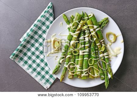 Fresh asparagus dish with sliced onion on white plate with checkered cotton serviette on grey table