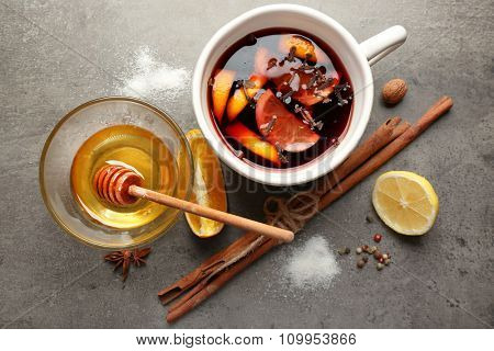 Tasty mulled wine in ceramic cup with citruses and cinnamon on the table