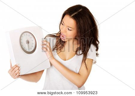 Shocked african woman holding a scale.