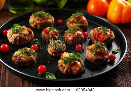 A frying pan with stuffed mushrooms and vegetables on the table