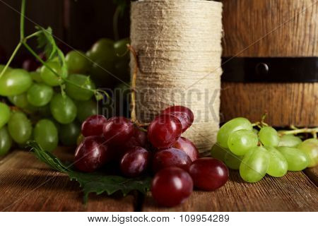 White and red grape with wine bottle on wooden background