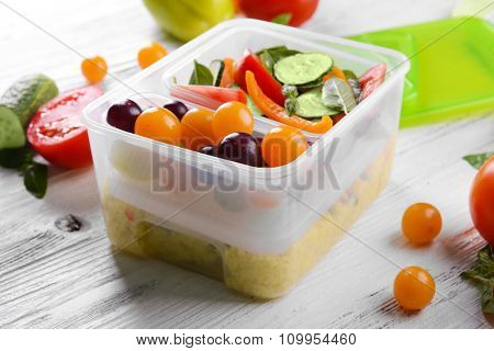 Tasty lunch in plastic containers on wooden table close up