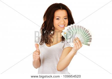 African woman holding polish money with thumbs up.