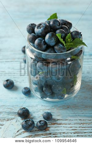 Fresh blueberries in jar on wooden table close up
