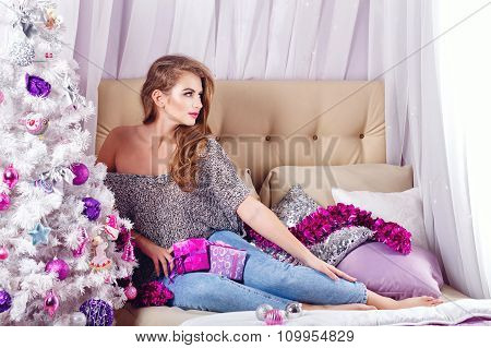 Girl Sits On A Couch Near The Christmas Tree.