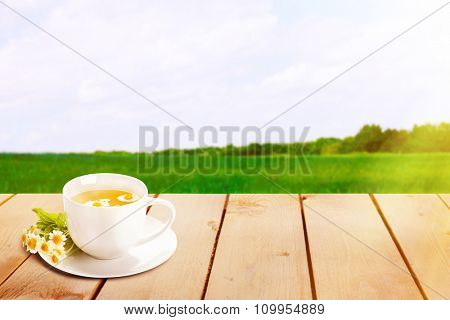 Cup of tea on wooden table, on nature background