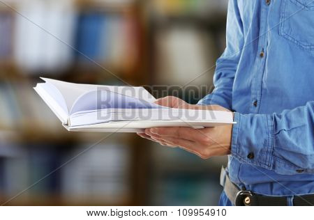 Male hands holding open book on bookshelves background
