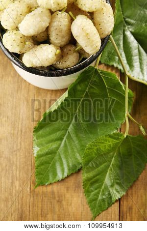 Ripe mulberries in mug with green leaves on table close up