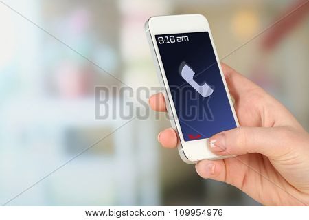 Hand holding mobile smart phone on abstract background