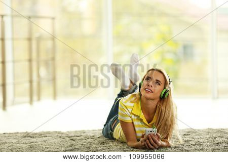 Young woman on the floor in a room listening to music