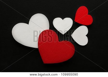 Red and white paper hearts on black background