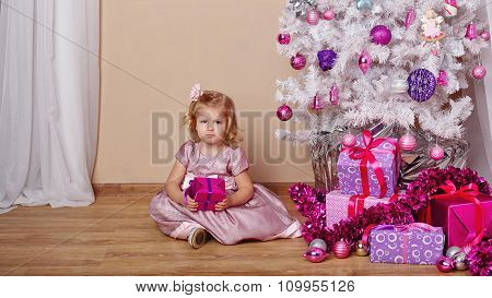 Little Girl With A Gift Near The Christmas Tree.