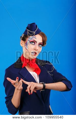 Stewardess With Face Art Considers Fingers.