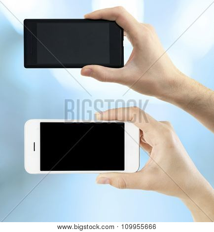 Hands holding black and white smart phones on light background