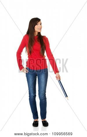 Beautiful student woman pointing down with a big pencil.