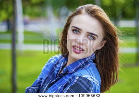 Portrait close up of young beautiful woman in a checkered blue shirt, summer outdoor