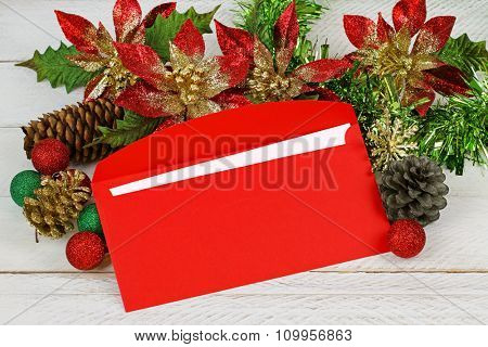 A red envelope with white paper inside on top of glittery Christmas decoration on white wooden background