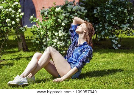 Young beautiful brown haired woman in blue shirt and jeans short sitting on green grass