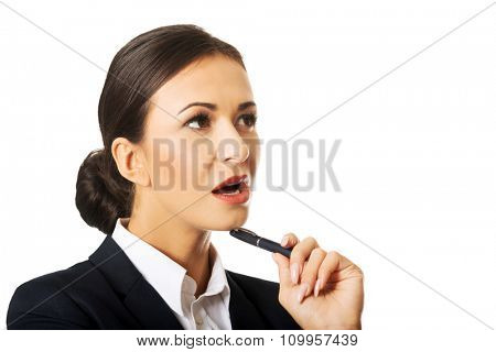 Pensive businesswoman holding a pen under chin.