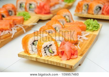 Maki sushi rolls set served on wooden board, closeup with selective focus, bokeh