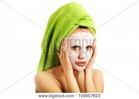 Spa woman with face mask and towel on head.