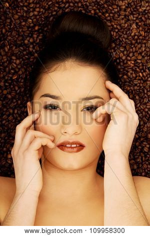 Attractive woman lying in coffee grains touching face.