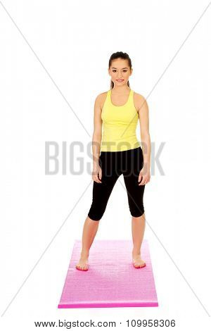 Attractive fitness woman on exercise mat.