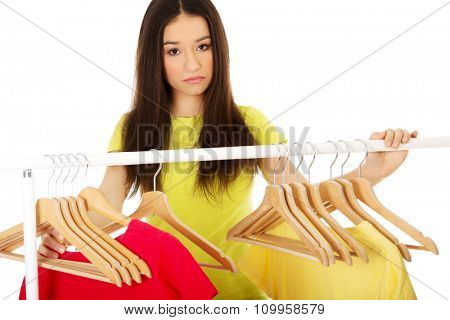 Young confused woman thinking what to dress.