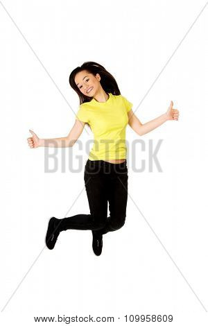 Young happy student woman jumping showing thumbs up.