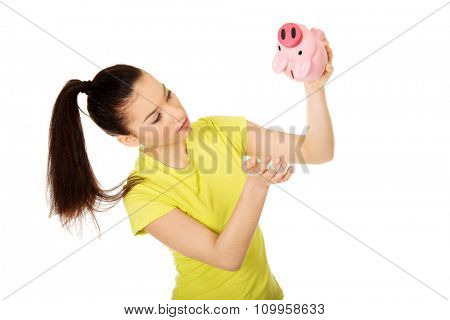 Sad teenage woman shaking piggybank for coins.