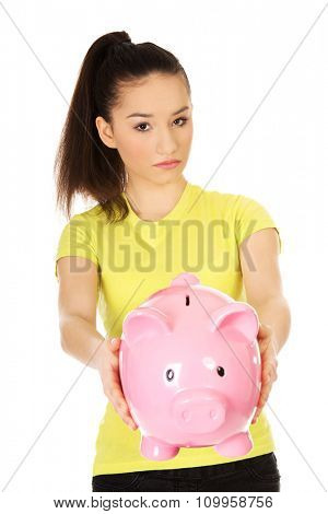 Sad teenage woman holding piggybank.
