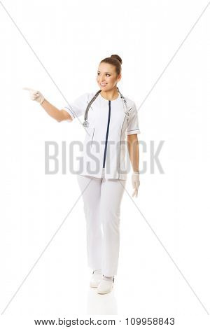 Smiling female doctor pointing to the right.
