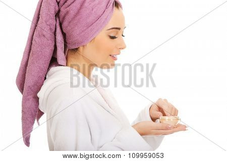 Spa woman in bathrobe and turban with cream moisturizer.