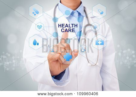 Doctor hand touching HEALTH CARE sign on virtual screen. medical concept