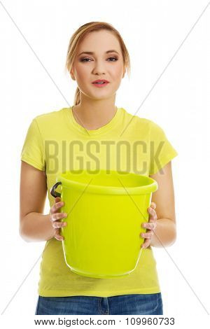Young student woman holding green bucket.