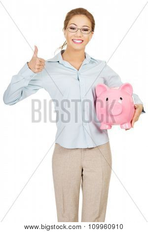 Business woman holding piggy bank with thumbs up.