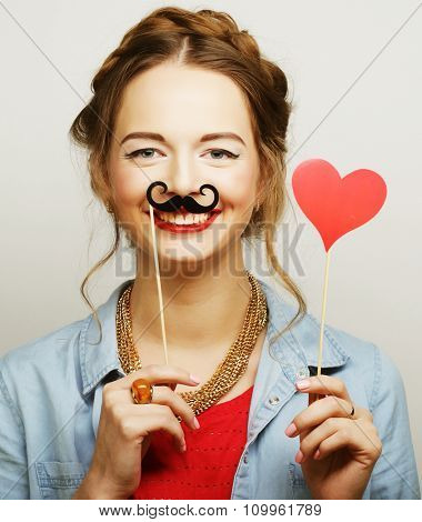 Girl wearing fake mustaches. Ready for party