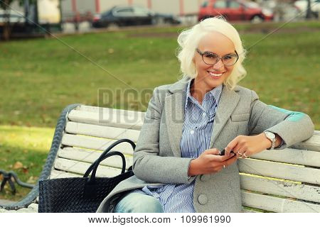 Young blond woman using a smart phone outdoors, autumn day