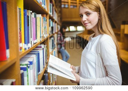 Blond student reading book in library at the university